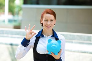 Closeup portrait happy, smiling business woman, bank employee holding piggy bank, isolated outdoors corporate office background. Financial savings, banking concept. Positive emotion face expression